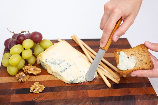 Hand spreading blue cheese on bread over cutting board