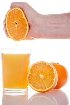 白い壁に隔離されたガラスに新鮮なオレンジジュースを手で絞った