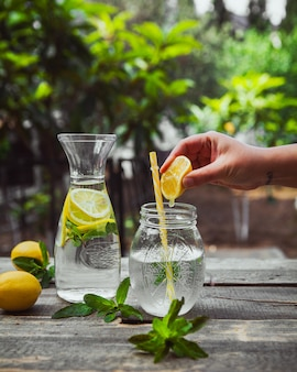 Hand squeezing lemon into water in glass jar side view on wooden and garden table