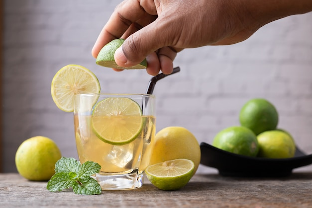 Hand squeezing lemon juice and sliced lemon, concept of healthy care.