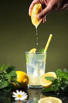 Hand squeezing lemon in lemonade, on dark background.