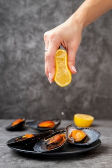 Hand squeezing lemon on mussels