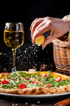 Hand squeezing lemon on a pizza