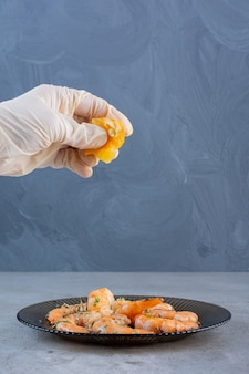 Hand squeezing lemon in a plate of delicious shrimps on a stone background.