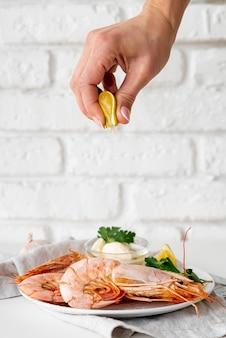 Hand squeezing lemon on shrimps