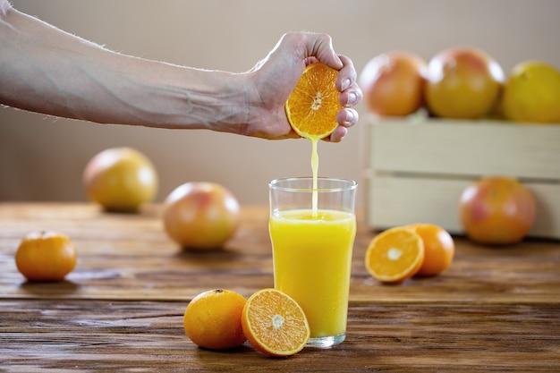 Рука выжимает апельсиновый сок в стакан на деревянном столе