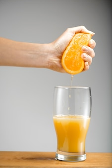 Hand squeezing out juice from orange into glass