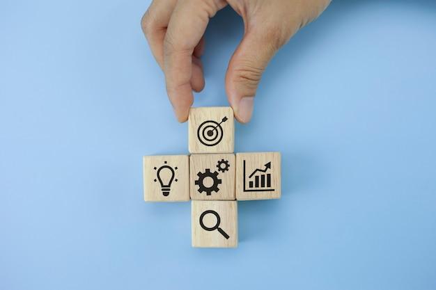 Ручной стек лесной блок шаг на столе с иконкой бизнес-стратегии и плана действий