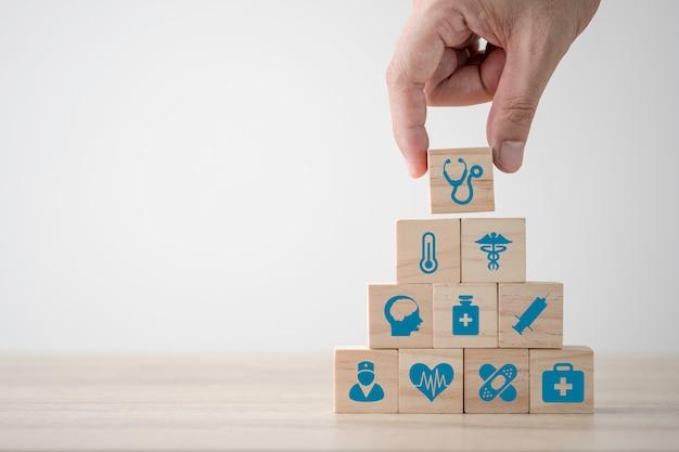 テーブルの上の木製キューブに画面を印刷した医療医学と病院のアイコンをスタッキング手。医療保険事業と投資。スペースのコンセプトをコピーします。