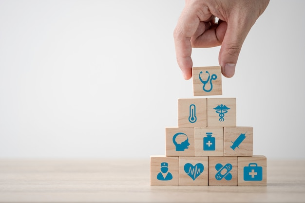 Hand stacking healthcare medicine and hospital icon which printed screen on wooden cubes on table. health care insurance business and investment. copy space concept.