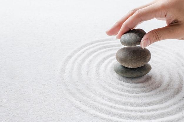 모래 웰빙 배경에 선 돌을 쌓는 손