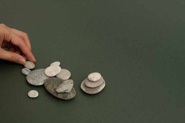 砂のウェルネスの背景に禅の石を手で積み重ねる