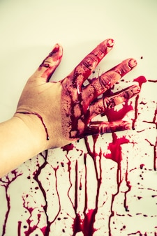 Hand stained with blood touching a wall