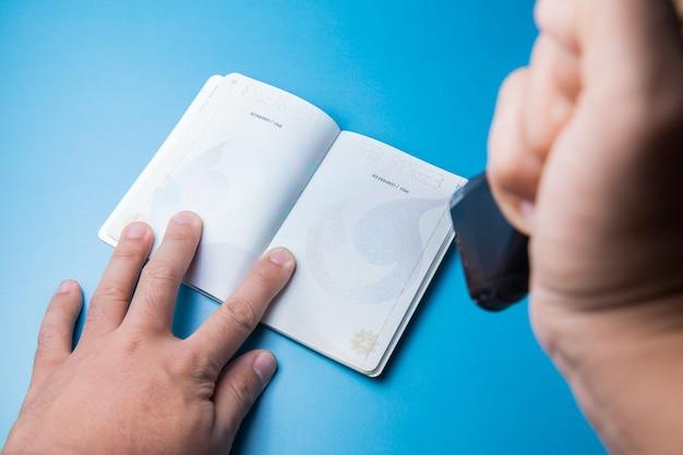 青い背景に空白のパスポートを手でスタンプ
