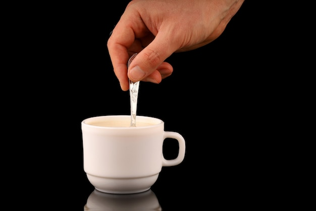 Hand stirs cappuccino in a cup