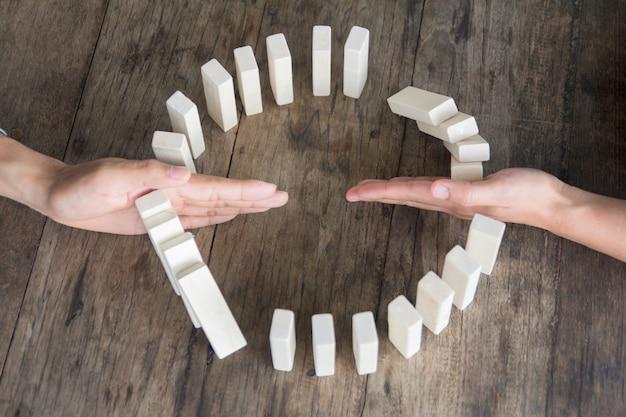Ручная остановка эффекта домино деревянных блоков для концепции бизнеса и подотчетности.