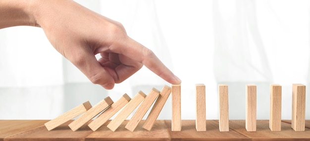 Hand stopping the domino effect stopped by unique, business ideas