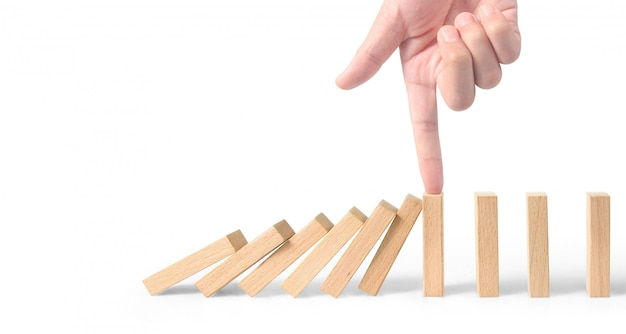 Hand stopping the domino effect stopped by unique
