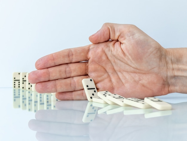 Hand stopping domino effect on white background