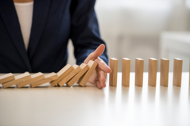 Hand stopping falling blocks on table
