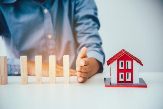 手を止めると、木のブロックが家に落ちるリスク、住宅保険、セキュリティ、リスク管理のコンセプト。