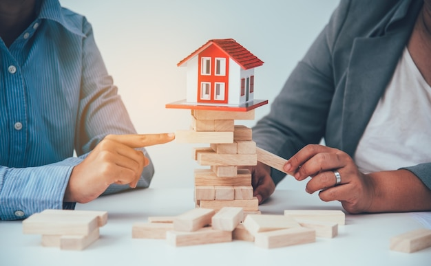 Hand stopping risk the wooden blocks from falling on house, home insurance ,security and risk management concept.