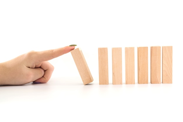Hand stopping wooden domino business crisis effect or risk protection concept.