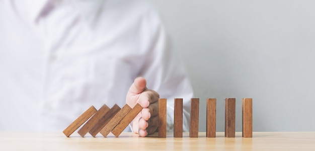 Hand stopping wooden domino business crisis effect or risk protection