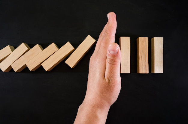 Hand stops falling wooden blocks  on black