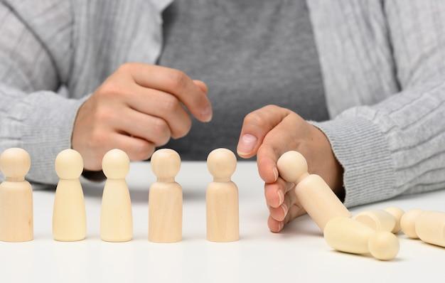 手は白い背景の上の男性の置物の落下を停止します。不平等な困難に耐えることができる強くて勇気ある性格の概念。強力なビジネス、状況の管理