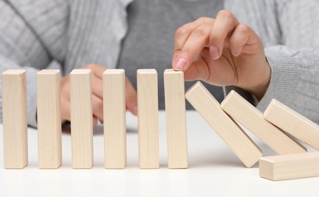 手は白い背景の上の木製のブロックの落下を停止します。不平等な困難に耐えることができる強くて勇気ある性格の概念。強力なビジネス、状況の管理