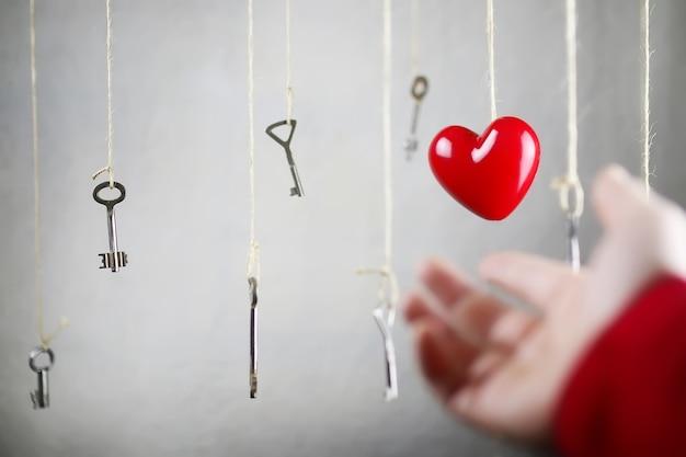Рука тянется к одному из многих старых старинных ключей, висящих на нитках