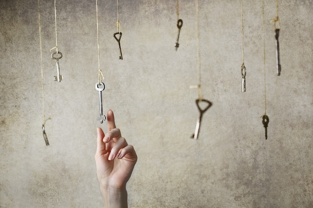 Hand stretching for one of the many old vintage keys hanging on threads