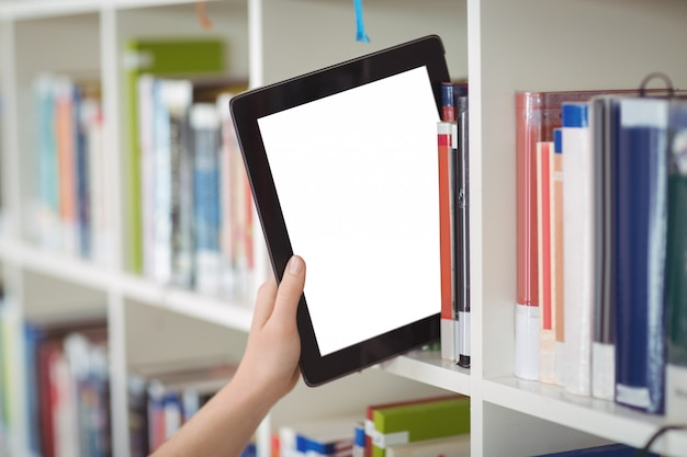 Hand of student keeping digital tablet in bookshelf in library