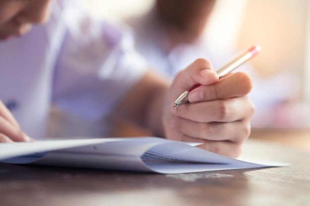 Hand of students writing exam in classroom with stress