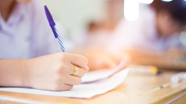 Hand of students writing and taking exam with stress in classroom