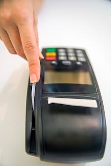 가 게에서 신용 카드를 강타하는 손. 신용 카드와 은행 터미널 여성 손. pos 및 신용 카드의 컬러 이미지.