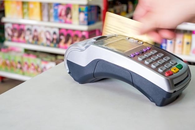 슈퍼마켓의 결제 단말기에서 손으로 신용 카드를 긁는다