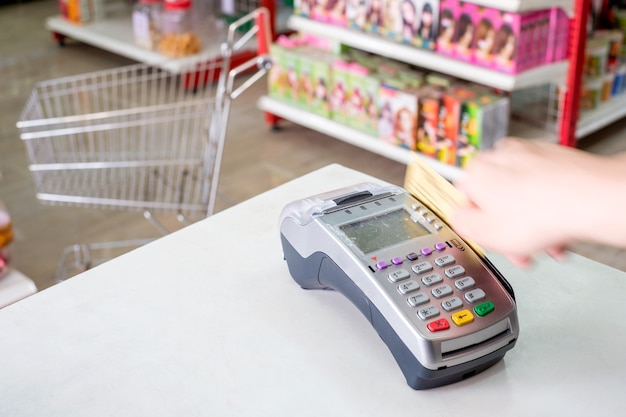 Hand swiping credit card on payment terminal in supermarket