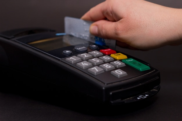 Hand swiping credit card in store. female hands with credit card and bank terminal. color image of a pos and credit cards.