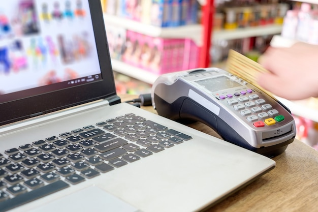 Hand swiping credit card on ternimal and using laptop payment shopping online