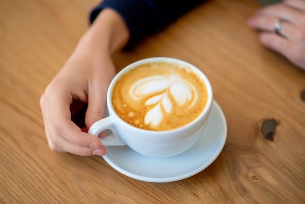 Hand on the table a cup of coffee