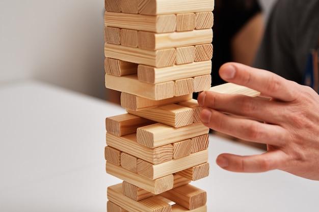 手は白い背景の家族の娯楽ボードゲームの木の塔から1ブロックを取る