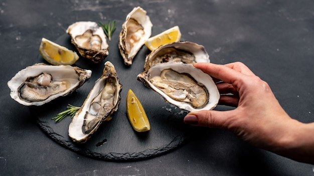 Hand take raw opened oyster from black platter with shelfish and lemon