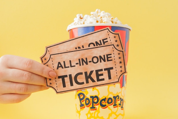 手は黄色の背景に紙コップから映画のチケットとポップコーンを取ります。女性はポップコーンを食べる。シネマコンセプト。フラット横たわっていた。