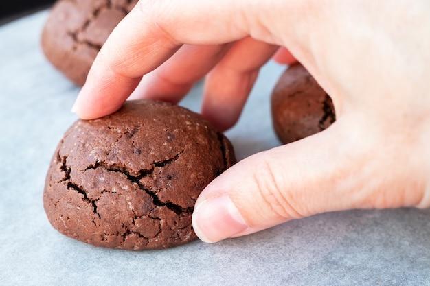 Рука берет испеченное треснувшее круглое шоколадное печенье с противня с пергаментной бумагой.