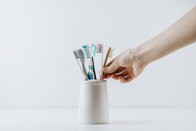 Hand takes eco friendly toothbrush from a white cup