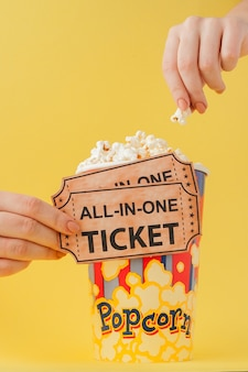 Hand takes a movie tickets and popcorn from a paper cup on a yellow . woman eats popcorn. cinema . flat lay. copyspace
