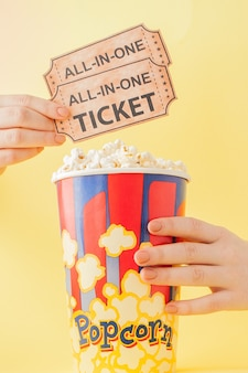 Hand takes a movie tickets and popcorn from a paper cup