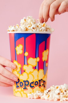 Hand takes a popcorn from a paper cup on pink.
